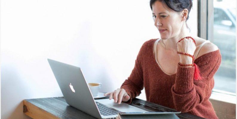ældre kvinde sidder og prøver at bruge computeren